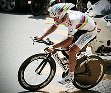 A cyclist wearing a rainbow skinsuit while riding his bike up a hill.