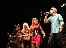 A group of musicians perform on a lighted stage. From left to right: a short-haired man plays bass guitar, a blond-haired woman plays the bongos, an red-haired woman holds a microphone, and a man wearing sunglasses and a blue shirt sings into a microphone.