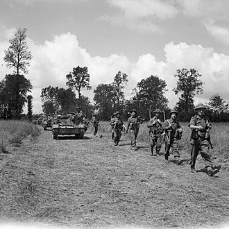 Operation Bluecoat - Universal carriers and infantry of the 15th (Scottish) Infantry Division move forward during Operation Bluecoat, 30 July 1944.