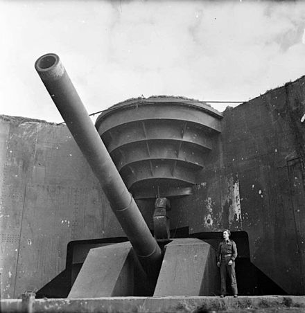 A British soldier poses next to the recently captured German 380mm gun Todt Battery at Cap Gris Nez. The British Army in North-west Europe 1944-45 B10467.jpg