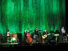 The Decemberists perform in formal attire on a green stage