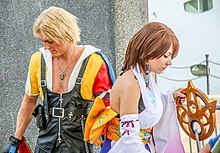 Young man and woman wearing clothes from a video game. The left one wears a skimpy yellow outfit while the woman wears a white Furisode
