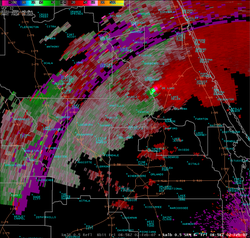 A Doppler radar image indicating the likely presence of a tornado over DeLand, Florida. Green colors indicate areas where the precipitation is moving towards the radar dish, while red areas are moving away. In this case the radar is in the bottom right corner of the image. Strong mesocyclones show up as adjacent areas of bright green and bright red, and usually indicate an imminent or occurring tornado. When these bright colors are one against the other on a radar display when in association with rotation, it is called a Tornado vortex signature.