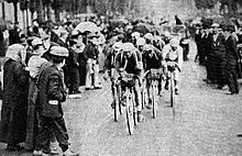 A group of cyclists, with spectators on the left and on the right.
