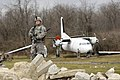U.S. Army Spc. Corey Munsinger, with a site security team, Charlie Company, Task Force Raptor, provides security while his team searches a downed aircraft for sensitive items during a training scenario at Camp 120119-A-FG822-010.jpg