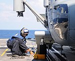 U.S. Navy Seaman Damaris M. Urena secures an MH-60S Seahawk helicopter attached to Helicopter Sea Combat Squadron (HSC) 9 aboard the guided missile cruiser USS Philippine Sea (CG 58) in the Atlantic Ocean 130807-N-XE109-261.jpg