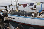 U.S. Sailors assigned to the guided missile destroyer USS Mason (DDG 87) toss food to fishermen aboard a dhow during a visit, board, search and seizure operation Nov. 21, 2013, in the Gulf of Aden 131121-N-PW661-020.jpg