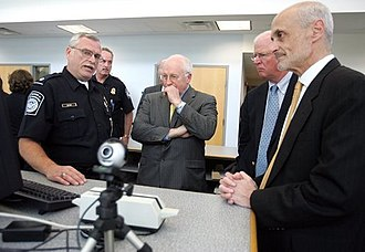 United States Department of Homeland Security - A U.S. Customs and Border Protection Officer addresses Dick Cheney (center), then Vice President of the United States, Saxby Chambliss (center right), a U.S. Senator from Georgia and Michael Chertoff (far right), then United States Secretary of Homeland Security, in 2005
