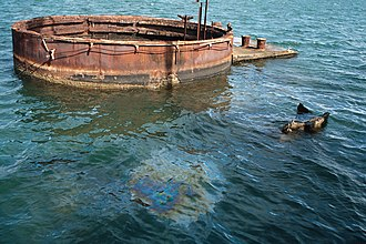 "USS Arizona Memorial - The ""tears of the Arizona"". Oil slick visible on water's surface above the sunken battleship."