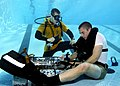US Navy 050209-N-3093M-004 Naval Diving and Salvage Training Center instructor stands ready to offer assistance to a diver student if he is not able to regain his own air supply during a problem solving exercise at the pool con.jpg