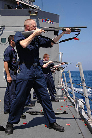 Tactical light - A U.S. Navy sailor fires a Mossberg 590 riot shotgun equipped with a tactical light integrated into the forend