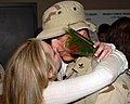 US Navy 060424-N-8909B-001 Engineman 2nd Class Timothy A. Hoisington, assigned to Mobile Security Squadron Three, embraces his wife after returning from a six-month deployment.jpg