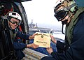 US Navy 070202-N-0535P-023 Hull Maintenance Technician 2nd Class Eryk Grenier receives his Honorable Discharge certificate from Chief Engineer Cmdr. Michael Kinsey while reenlisting in an SH-60 Seahawk.jpg