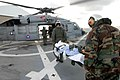 US Navy 070701-N-4238B-004 Aviation Warfare Systems Operator 2nd Class Trevor Ahrendt, attached to Helicopter Sea Combat Squadron (HSC) 28, and Tech. Sgt. Michael Cooper carry a patient.jpg