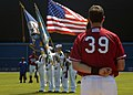 US Navy 070814-N-9116H-010 A baseball player watches as the nuclear-powered aircraft carrier USS Theodore Roosevelt (CVN 71) color guard parades the colors during the pre-game national anthem.jpg