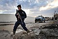 US Navy 081220-N-1810F-342 An Iraqi policeman steps over trash and mud during a walking patrol.jpg