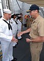 US Navy 090630-N-0486G-003 Adm. Jonathan W. Greenert, commander, U.S. Fleet Forces Command, presents a coin to Interior Communications Electrician 2nd Class Ronald Remillard during a visit to the guided-missile destroyer USS Fa.jpg