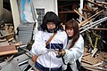 US Navy 110315-N-2653B-138 A mother and daughter look at a family photo amid the wreckage of their home.jpg