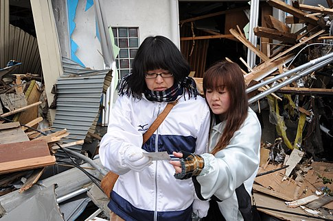 A mother and daughter look at a family photo amid the wreckage of their home. Image: U.S. Navy.