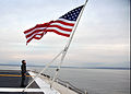 US Navy 111211-N-YB753-021 Quartermaster 3rd Class Shea Morgan faces the national ensign as the Nimitz-class aircraft carrier USS Abraham Lincoln (.jpg