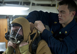 US Navy 120109-N-DR144-061 Chief Machinist's Mate Daniel Pike helps a Sailor don a firefighting ensemble.jpg