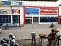 Vue de dos d'une Vendeuse de fruits en face d'une boutique de vente de lubrifiants au Bénin.jpg