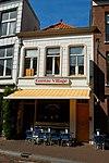 foto van Klein huis met rood schilddak en met gebosseerd witgepleisterde lijstgevel