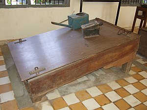 Waterboarding - Waterboard on display at the Tuol Sleng Genocide Museum: prisoners' feet were shackled to the bar on the right, wrists restrained by shackles on the left. Water was poured over the face using the watering can. The use of this type of waterboard is depicted in a painting by former Tuol Sleng prisoner Vann Nath, shown in that article.