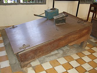 Enhanced interrogation techniques - Waterboard on display at the Tuol Sleng Genocide Museum: prisoners' feet were shackled to the bar on the right, wrists restrained by shackles on the left. Water was poured over the face using the watering can