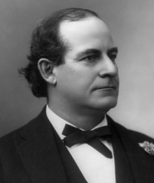A man in his early forties, with receding black hair, facing right and wearing a black bow tie, black coat, and white shirt