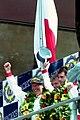 Winners Hurley Haywood, Mauro Baldi & Yannick Dalmas on the podium at the 1994 Le Mans (31130244344).jpg