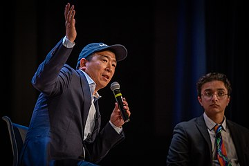 Yang is holding a microphone while gesturing and making a speech