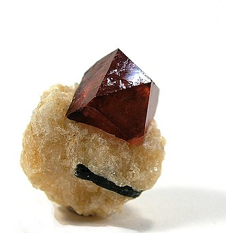 Zircon - A lustrous crystal of zircon perched on a tan matrix of calcite from the Gilgit District of Pakistan
