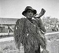 """""""Čred?nk"""" (kravji pastir za skupno pašo na gmajni"""") z rogom in v starem plašču iz trave plaščinke zoper dež (rekonstrukcija noše pastirja), Kostanjevica 1956 (2).jpg"""