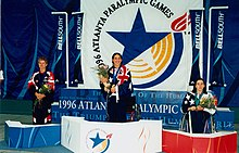 Three women stand holding flowers over their heads on a medal stands