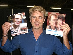 A blond-haired middle-aged man wearing a blue shirt, holding two large photographs of himself