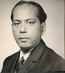 Black-and-white photo of the head and shoulders of a middle-aged man. Brown skin, receding hairline, short dark hair.  He is wearing a suit and looking at the camera with a calm but determined expression.