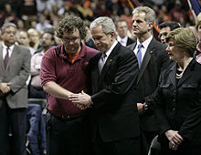 President Bush clasping one of the hands of a student in both of his; President Bush's wife, Laura, is to his left.