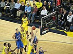 Two opposing basketball teams on a basketball court fight for a rebound. One team is in maize uniforms with the word Michigan on the front and names on the back and the other is light blue with the word Duke on the front and names on the back.