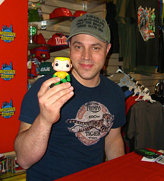 Geoff Johns - Johns holding up a Funko vinyl figure of Aquaman, one of the titles he wrote as part of The New 52