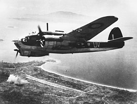 Twin-engined military aircraft in flight high over a seashore