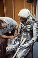 A NASA suit technician adjusts astronaut Gus Grissom's Mercury pressure suit.jpg