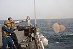A Sailor fires a .50-caliber machine gun at sea..jpg