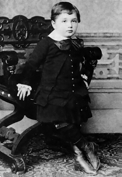A young boy with short hair and a round face, wearing a white collar and large bow, with vest, coat, skirt and high boots. He is leaning against an ornate chair.