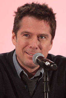 Alexis Denisof interprète Sandy Rivers.