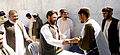 Amir Mohammad Akhundzada, center, the governor of Uruzgan province, Afghanistan, presents a new voter registration card to a Tarin Kowt resident in the province May 26, 2013 130526-D-ZZ999-001.jpg