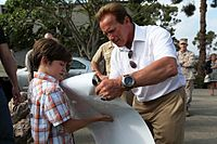 "Arnold Schwarzenegger signs a young boy's ""The Expendables 2"" poster, 2012.jpg"