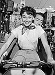 Audrey Hepburn and Gregory Peck on Vespa in Roman Holiday trailer (cropped).jpg