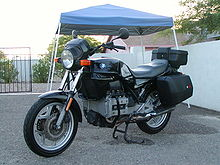 Black BMW K75T with topbox and panniers, parked on a driveway in front of a house and metal gates
