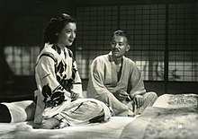Two seated Japanese persons in traditional dress: to the left, a young woman with dark hair facing right; to the right, an elderly looking gentleman with gray hair, looking at the woman. They are sitting on futons and a shoji screen is in the background.